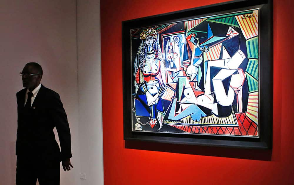 A security guard stands beside Pablo Picasso's Women of Algiers (Version O), which sold for nearly $179.4 million, making it set a world record for artwork at auction during a sale at Christie's Rockefeller Center in New York.