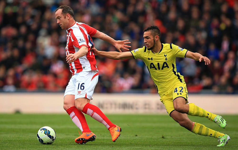 Stoke City's Charlie Adams and Tottenham Hotspur's Nabil Bentaleb battle for the ball during their English Premier League soccer match at the Britannia Stadium, Stoke On Trent, England.