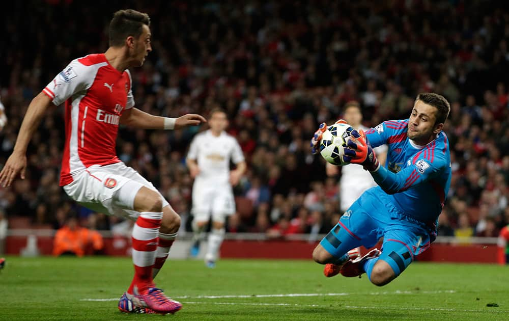 Swansea City's goalkeeper Lukasz Fabianski collects the ball as Arsenal's Mesut Ozil advances on him during their English Premier League soccer match between Arsenal and Swansea City at the Emirates stadium in London.