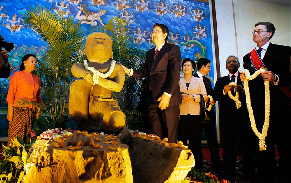 Cambodian Deputy Prime Minister Sok An, stands next to a 10th century Cambodian sandstone statue as the Director of the Cleveland Museum of Art William M. Griswold, holds a garland during a ceremony in Phnom Penh, Cambodia. The Cleveland Museum of Art on Tuesday handed over a 10th-century statue to Cambodia after it uncovered evidence the sculpture was probably looted during the country's civil war.