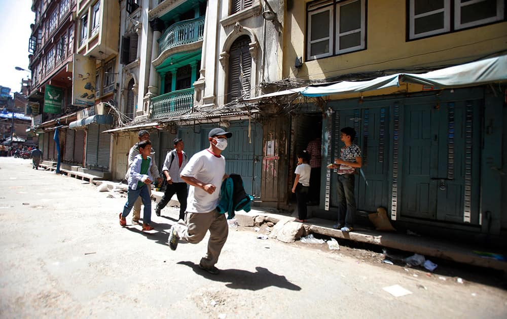 A Nepalese man runs to safety after a second earthquake hit Nepal in Kathmandu, Nepal.