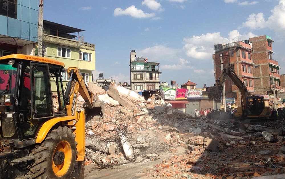 Earthmovers remove debris from a building that collapsed in an earthquake in Kathmandu, Nepal.
