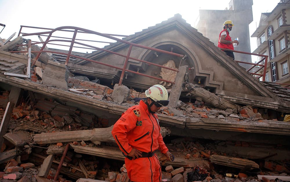 A Mexican rescue worker stands at the site of a building that collapsed in an earthquake in Kathmandu, Nepal.