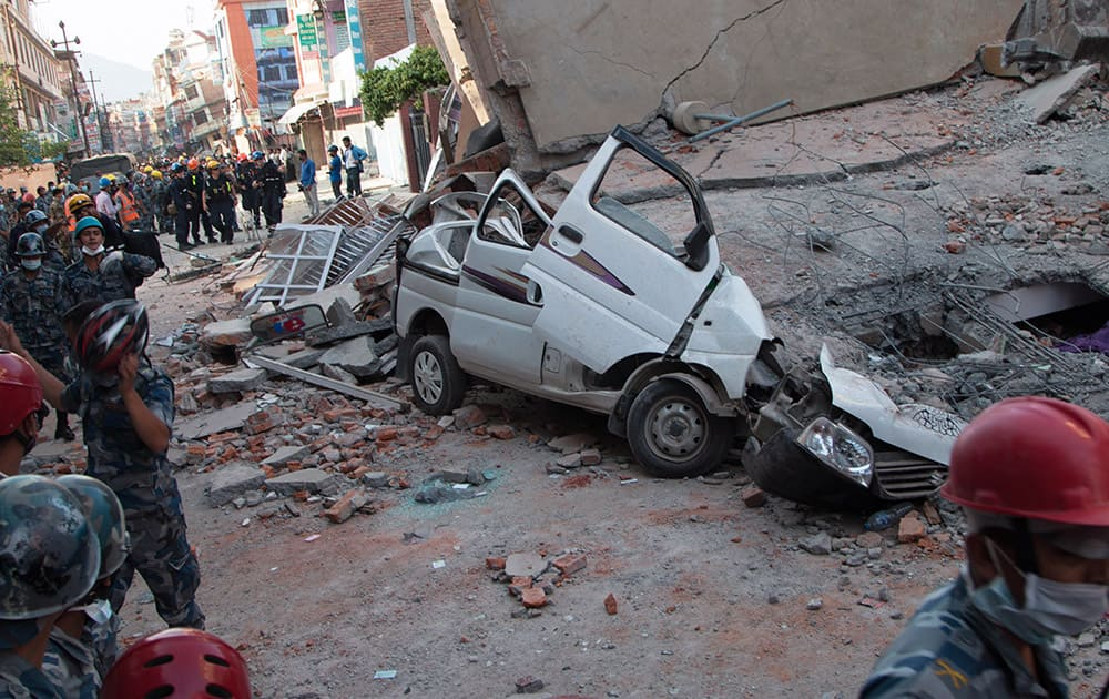 A car is seen smashed under the weight of a building that collapsed in an earthquake in Kathmandu, Nepal.