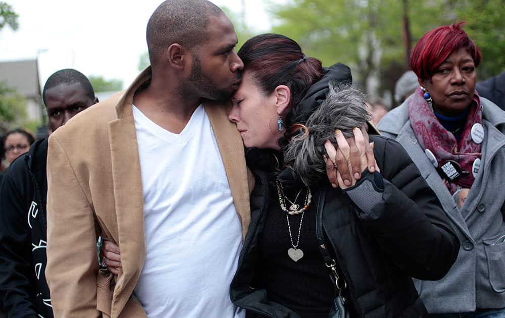 Jeff Jackson, left, comforts his girlfriend, Andrea Irwin, the mother of Tony Robinson, while escorting her during a protest march on Williamson Street, in Madison, Wis.