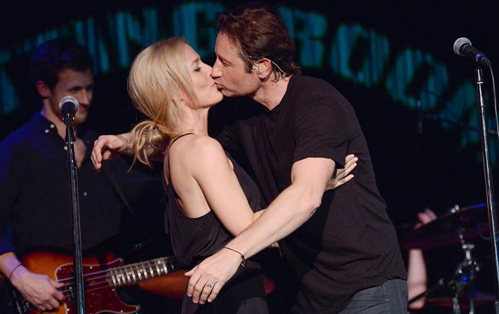 David Duchovny and actress Gillian Anderson kiss during their performance of Neil Young's