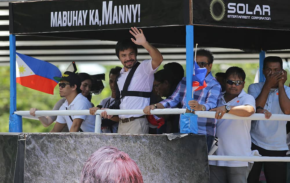 Filipino boxing hero Manny Pacquiao waves during a welcome parade as he arrives in Manila, Philippines. Pacquiao returned home to the Philippines on Wednesday nursing his right shoulder after surgery and weighing whether to retire or push for a rematch with Floyd Mayweather Jr.