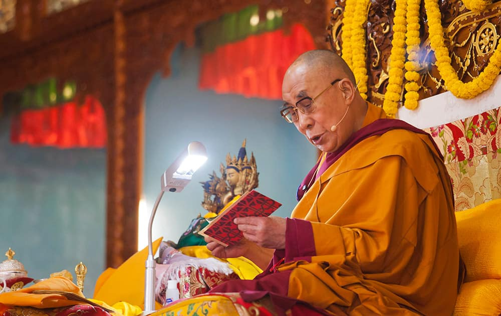 Tibetan spiritual leader the Dalai Lama reads from a Buddhist text during his religious talk at the Gyuto Monastery in Dharmsala.