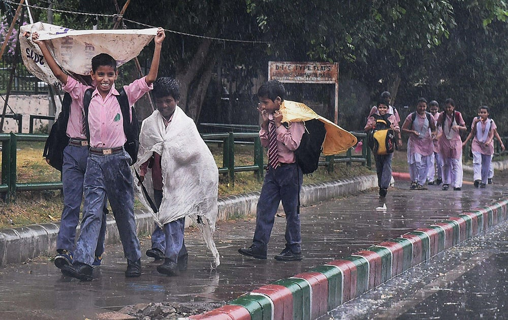 School children enjoying rain in New Delhi.
