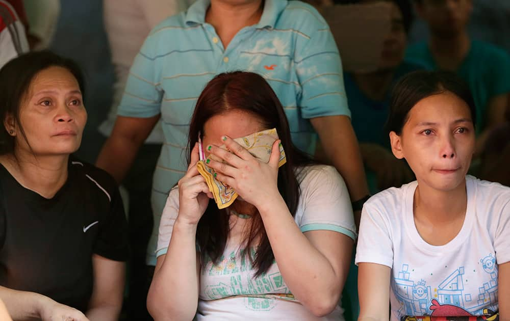 Relatives wait for news on the fate of their loved ones following a fire that gutted Kentex rubber slipper factory in Valenzuela city, a northern suburb of Manila, Philippines.