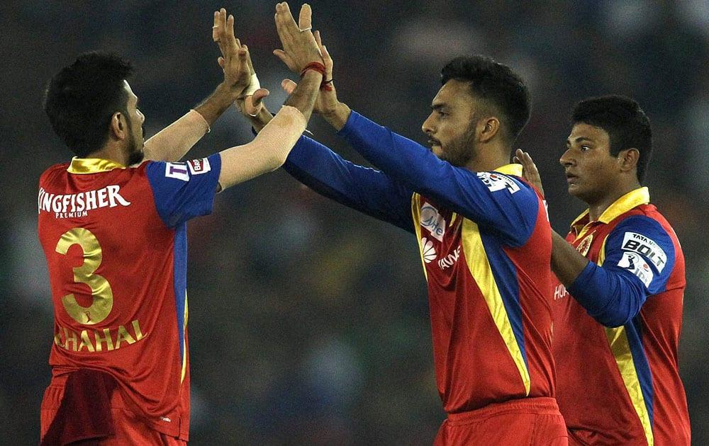 Yuzvendra Chahal of the Royal Challengers Bangalore congratulates Mandeep Singh of the Royal Challengers Bangalore for taking the catch to get Wriddhiman Saha of Kings XI Punjab wicket an IPL match in Mohali.