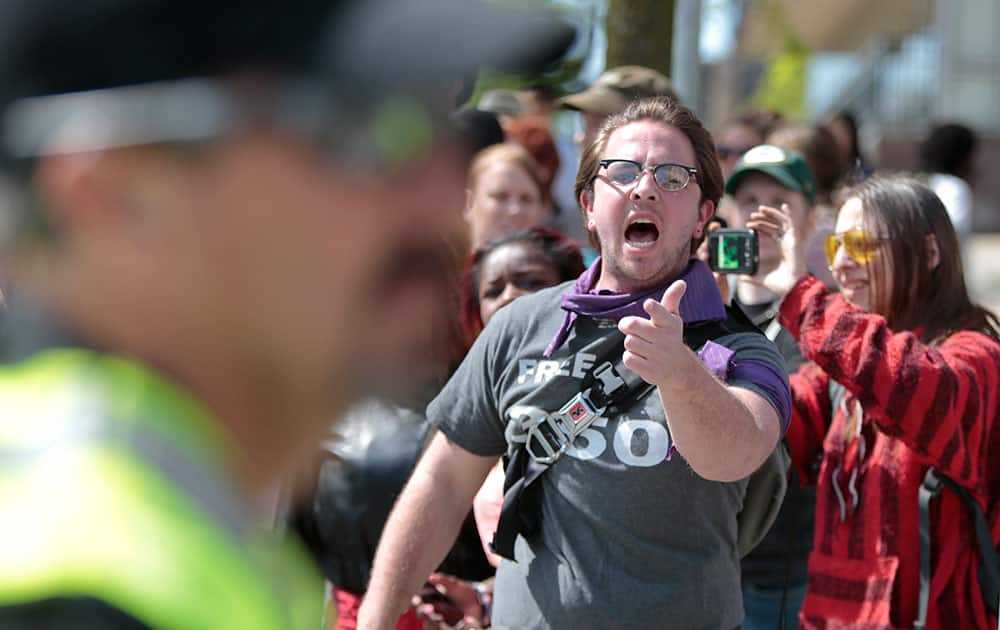 A protester yells at police as others are arrested during a protest in Madison, Wis.