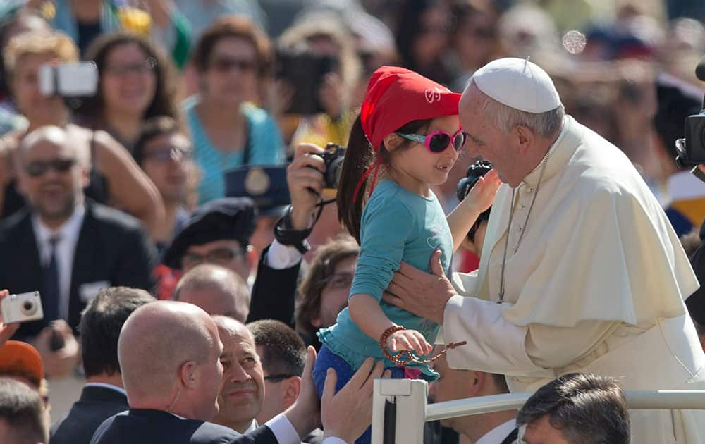 Pope Francis kisses a young girl as he arrives for his weekly general audience in St. Peter's Square at the Vatican.