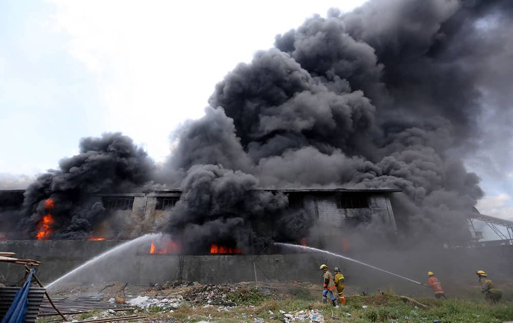 Firemen train their hoses at the burning Kentex footwear factory at Valenzuela city, a northern suburb in Manila, Philippines.