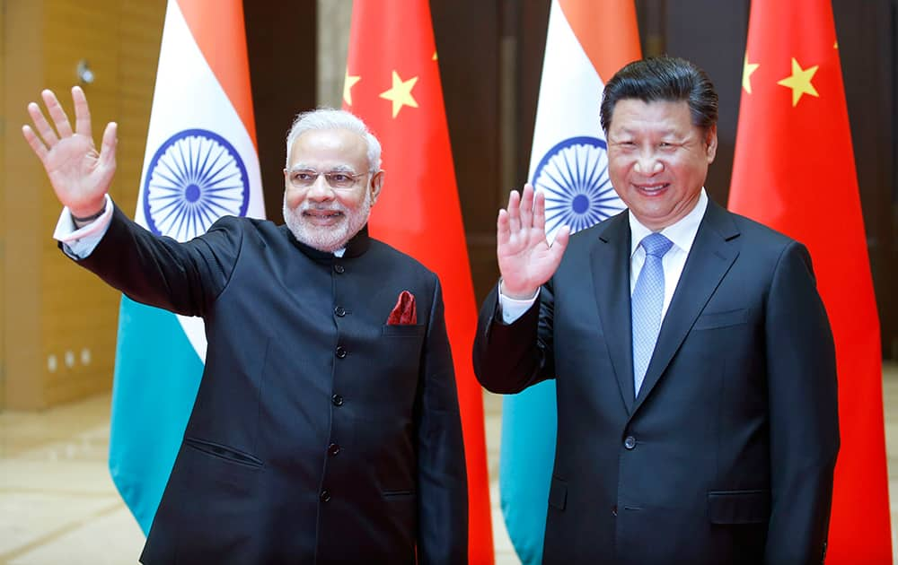 Prime Minister Narendra Modi and Chinese President Xi Jinping wave to journalists prior to their meeting in Xian, Shaanxi province, China.