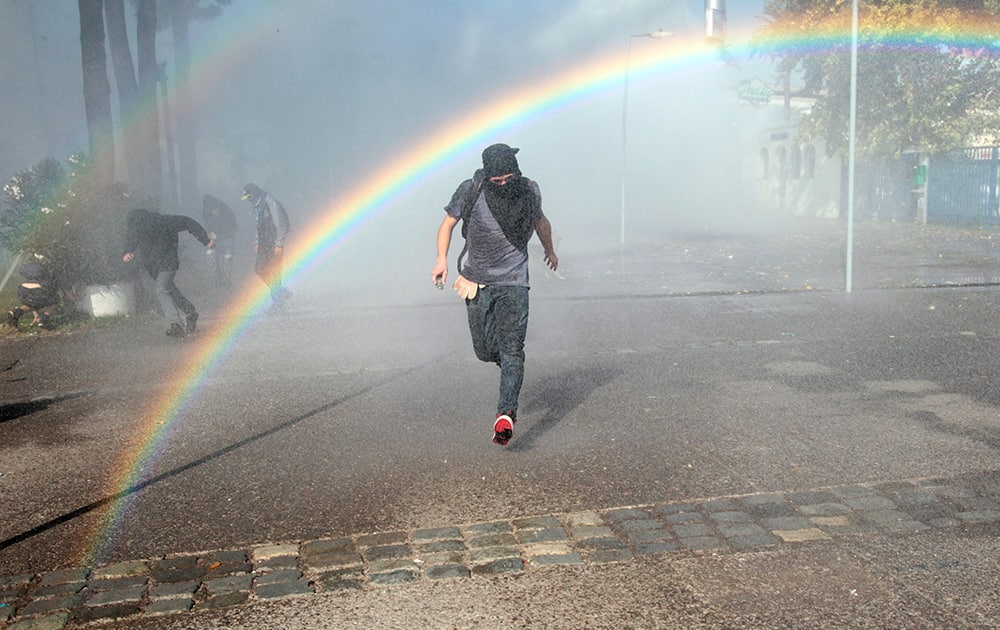 A protester runs from a jet of water shot from a police water cannon in the courtyard of the University of Santiago, during clashes between students and police, in Santiago