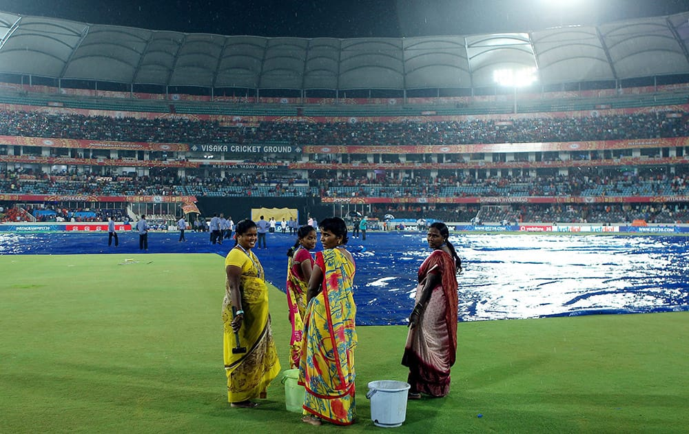 Ground staff wait for the rain to ease during IPL 8 match between Sunrisers Hyderabad and Royal Challengers Bangalore in Hyderabad.