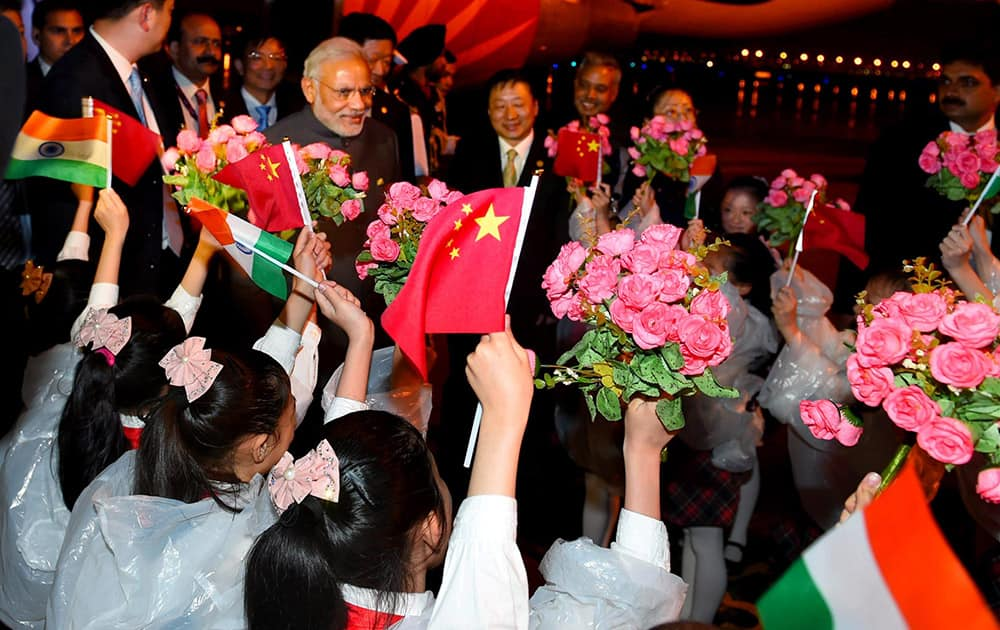 Prime Minister Narendra Modi being welcomed by children upon his arrival at Shanghai Honggiao International Airport in Shanghai.