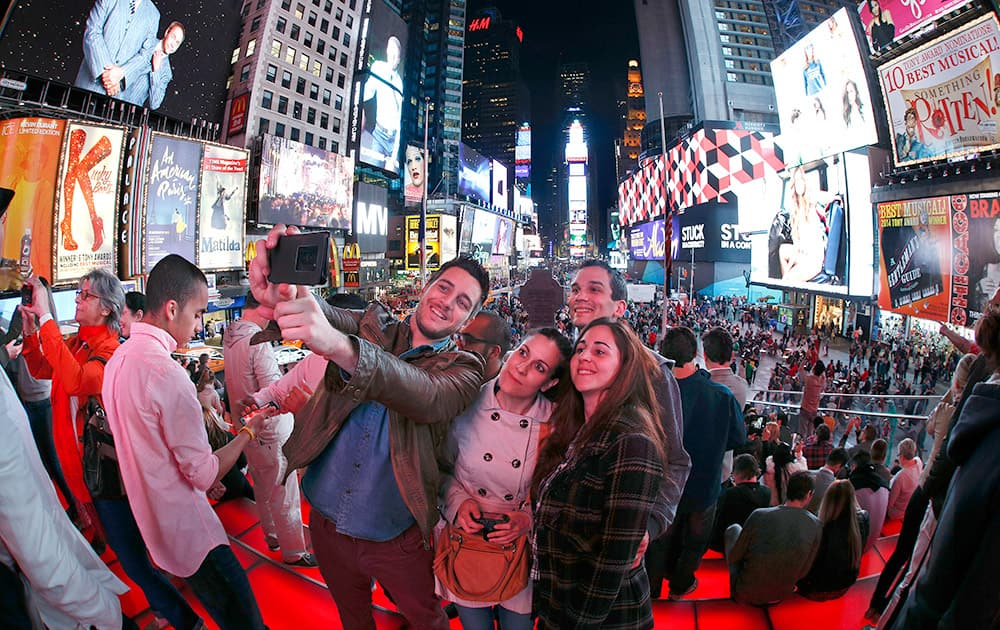 Tourists from Spain take a group selfie in Times Square, in New York. The neon lights of Broadway might not all shine so bright if a push to cut energy usage in the city's buildings comes to pass.