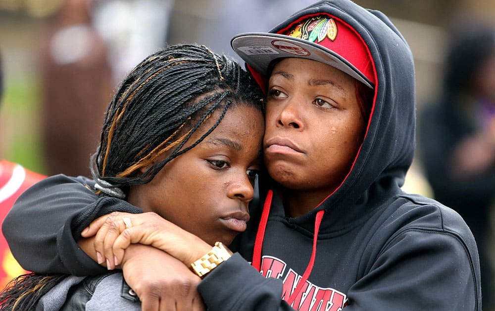 LaToya Howell of Waukegan, right, hugs her 12-year-old daughter Jayla as people, in Waukegan, Ill., protest the decision by Lake County State's Attorney Michael Nerheim not to file charges in the April police shooting of Howell's son Justus in nearby Zion.