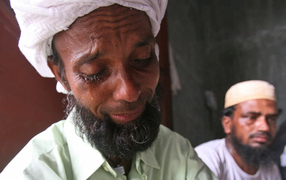 A Bangladeshi migrant weeps during the visit of Bangladesh's Ambassador to Indonesia Mohammad Nazmul Quaunine at a temporary shelter in Langsa, Aceh province, Indonesia