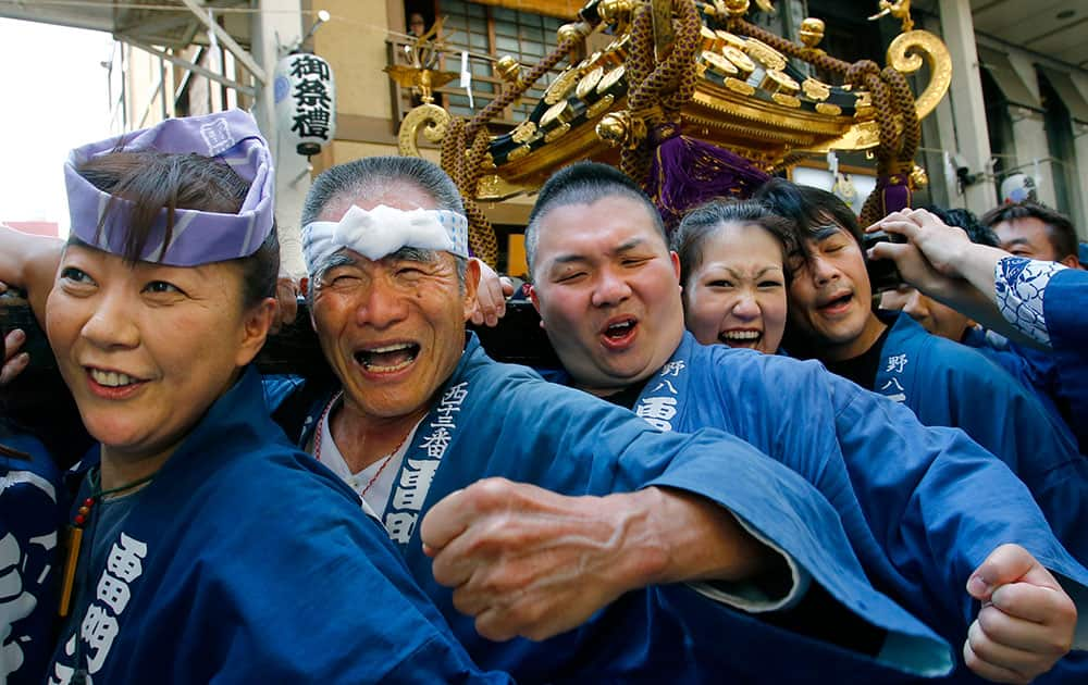 Participants clad in traditional happi coats carry a mikoshi, or portable shrine in the annual Sanja Festival parade through a street of Tokyo's Asakusa shopping district.