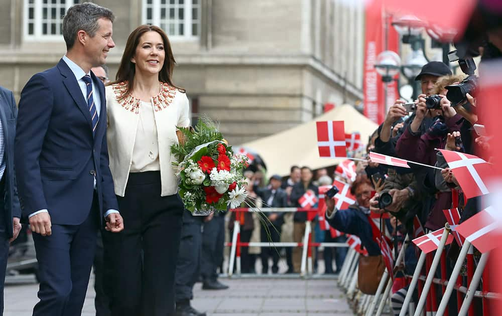 People wave Danish flags as Frederik, Crown Prince of Denmark and his wife Crown Princess Mary arrive at the city hall in Hamburg, Germany. The Danish royal couple is in Germany on a working visit entitled 'Danish Living' until May 21, 2015.