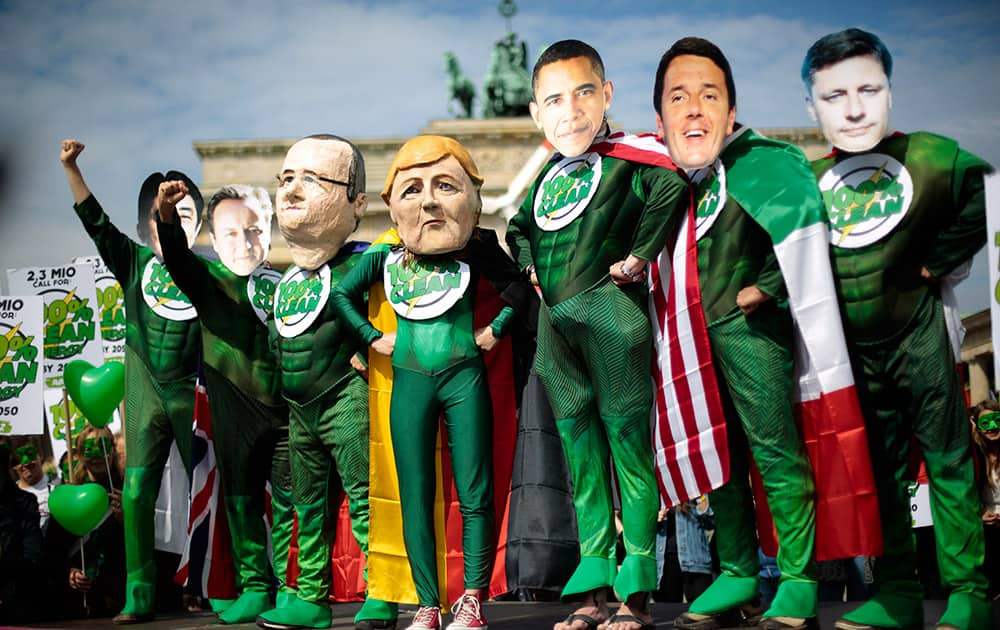 Climate activists in green costumes and with masks of the G7 leaders Japanese Prime Minister Shinzo Abe, Britain's Prime Minister David Cameron, French President Francois Hollande, German Chancellor Angela Merkel, US President Barack Obama, Italian Prime Minister Matteo Renzi and Canadian Prime Minister Stephen Harper, from left, attend a protest in front of the Brandenburg Gate near a building hosting the 'Petersberg Climate Dialogue' conference in Berlin, Germany.