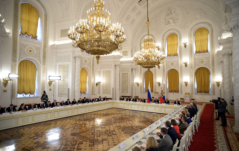 Russian President Vladimir Putin, center, between flags, chairs a meeting of the Council for Interethnic Relations and the Council for the Russian Language at the Kremlin in Moscow, Russia.