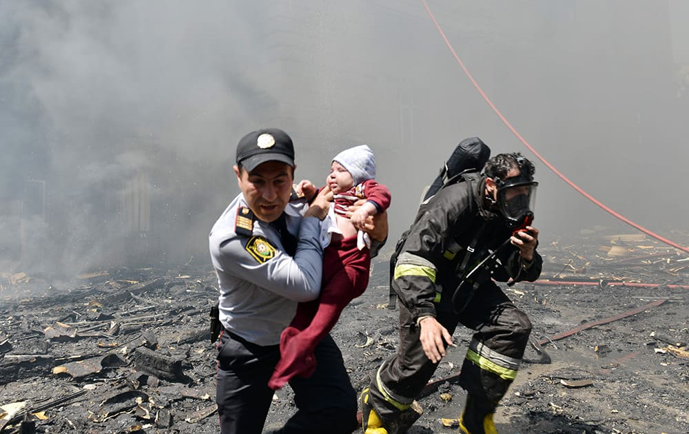A police officer and a fire fighter help child victim of an apartment building fire in Baku, Azerbaijan.