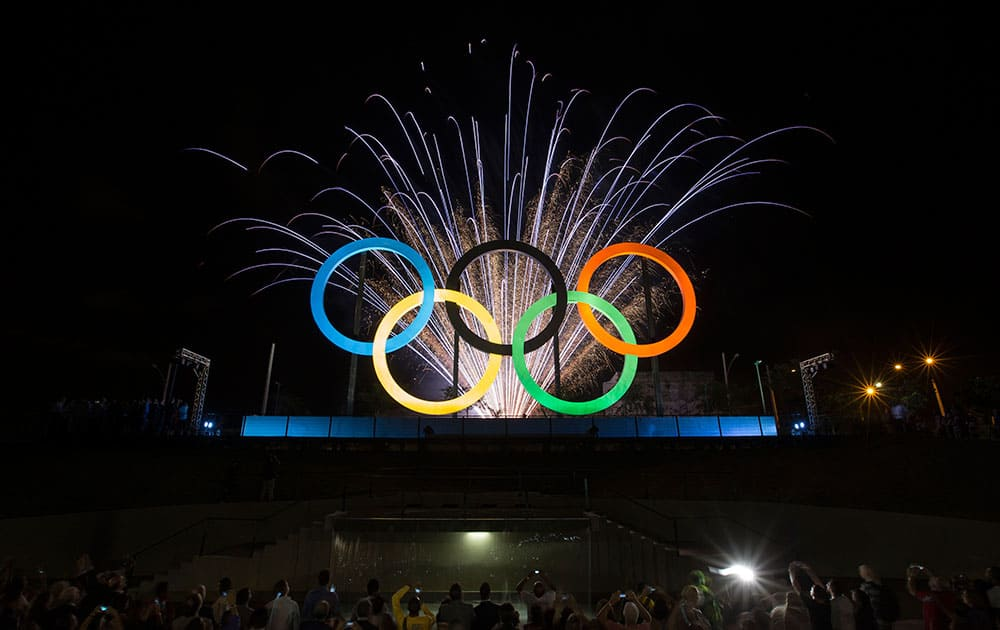 Fireworks explode behind the Olympic rings during their inauguration at the Madureira Park in Rio de Janeiro, Brazil.