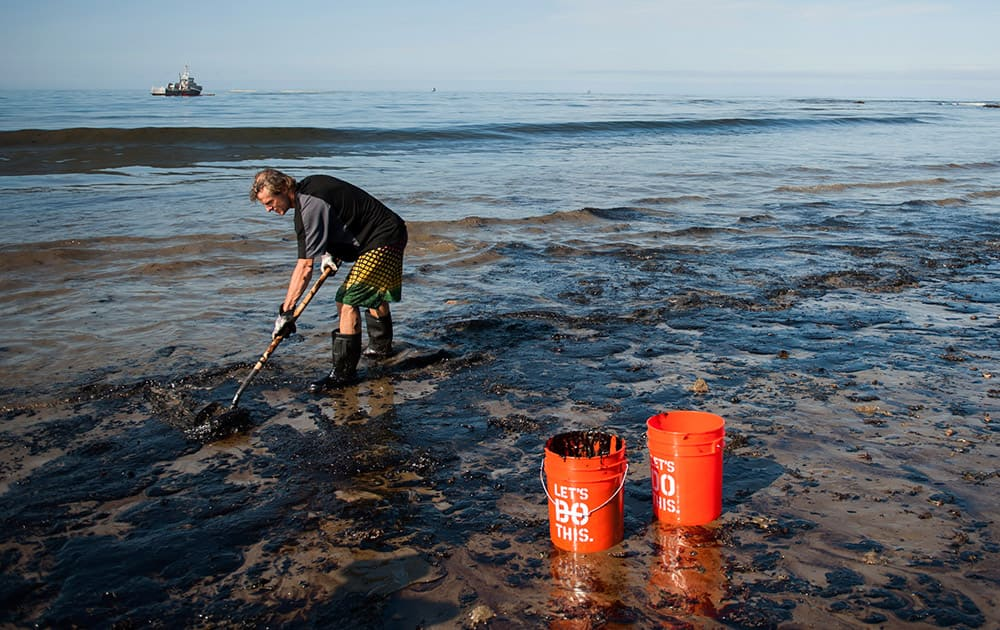 A man shovels up oil on a section of beach about a mile east of Refugio State Beach, Calif.