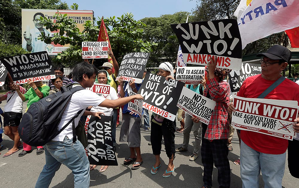 Protesters display placards during a rally at the Department of Agriculture to coincide with the visit in the country of Roberto Azevedo, Director General of the World Trade Organization (WTO), at suburban Quezon city, northeast of Manila.
