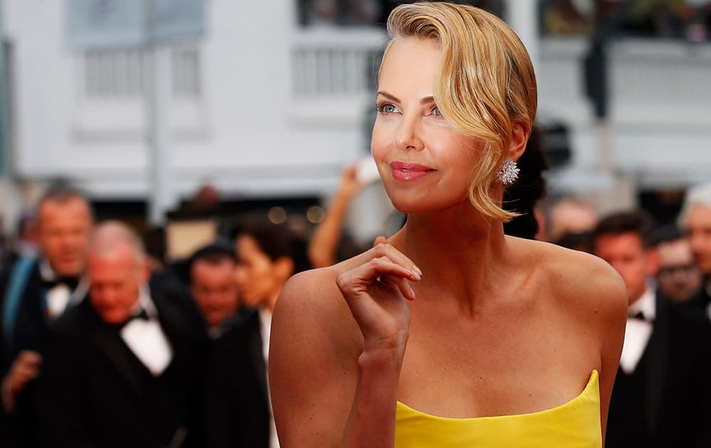 Actress Charlize Theron poses for photographers as she arrives for the screening of the film Mad Max: Fury Road at the 68th international film festival, Cannes, southern France.