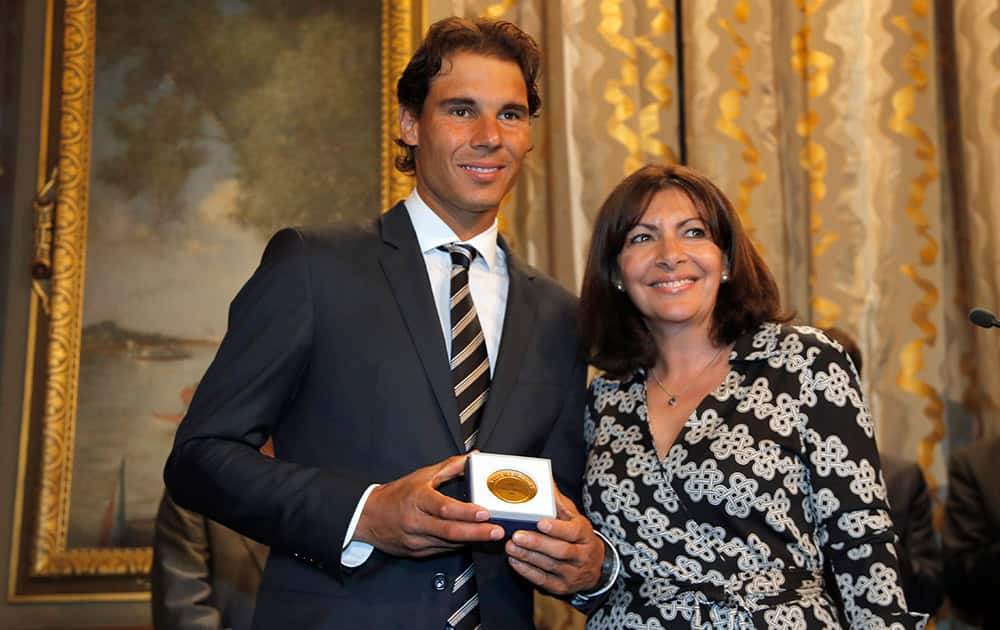 Tennis player Rafael Nadal poses with the Grand Vermeil Paris medal, he received from Paris Mayor Anne Hidalgo, right, during a ceremony at the Paris city Hall, in Paris.