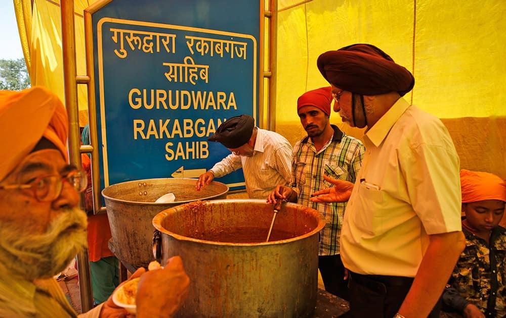 Sikhs distribute food to passersby to mark the martyrdom of Guru Arjan Dev in New Delhi.