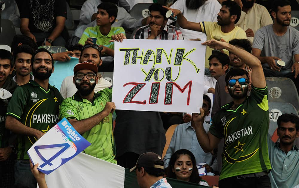 Pakistan's cricket fans hold up a poster to welcome the Zimbabwe cricket team at the Gaddafi stadium in Lahore, Pakistan.
