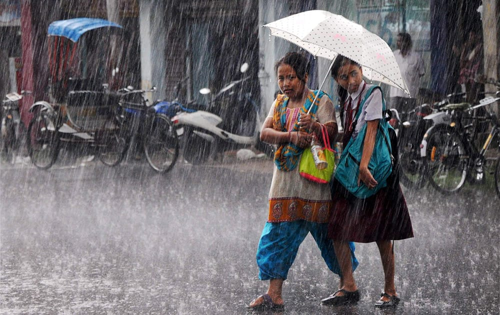 Young girls shelter under an umbrella during heavy rains in Agartala.