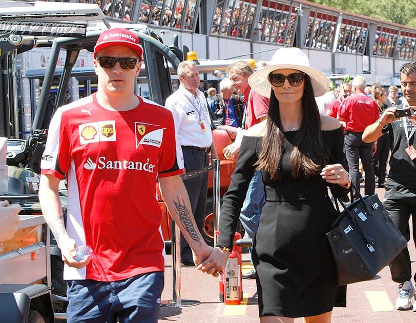 Ferrari driver Kimi Raikkonen of Finland walks with his partner Minttu Virtanenin after the autographs session at the Monaco racetrack, in Monaco.