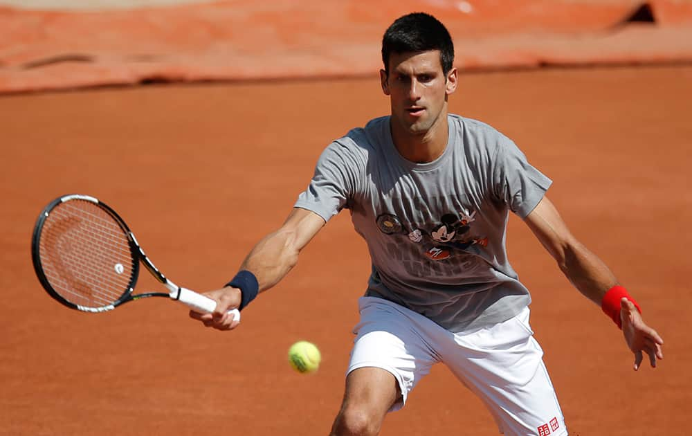 Serbia's Novak Djokovic returns the ball during a training session for the French Tennis Open at the Roland Garros stadium.