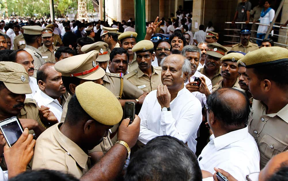 Fans and policemen surround south Indian film star Rajinikanth as he arrives to attend the swearing-in-ceremony of Jayaram Jayalalitha as the chief minister of Tamil Nadu state in Chennai.