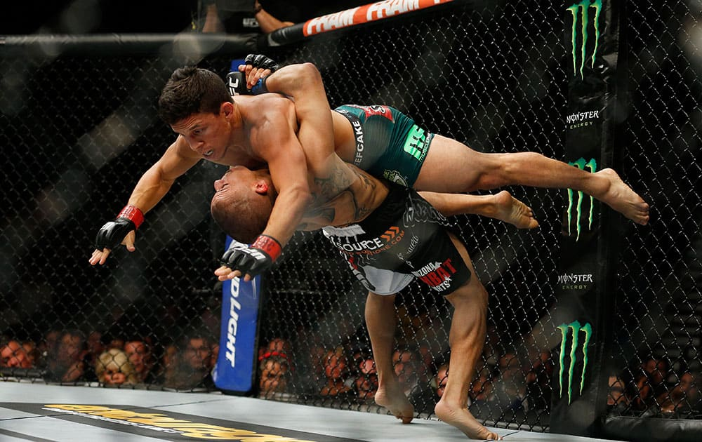 John Moraga, bottom, takes down Joseph Benavidez during their flyweight mixed martial arts bout at UFC 187 in Las Vegas.