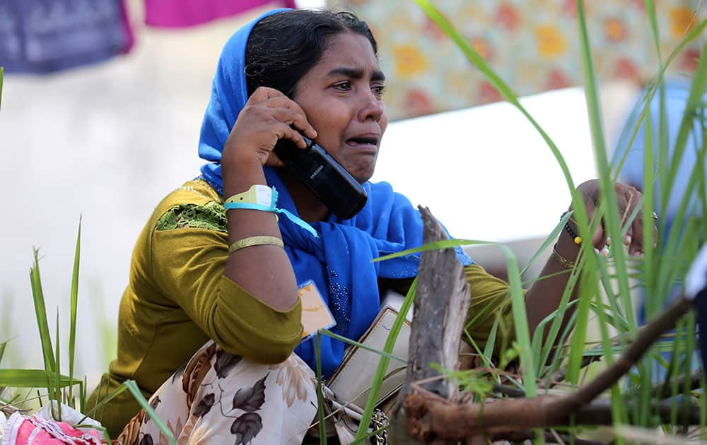 A Rohingya migrant woman cries as she talks with her relative on mobile phone at a temporary shelter in Kuala Langsa, Aceh province, Indonesia.
