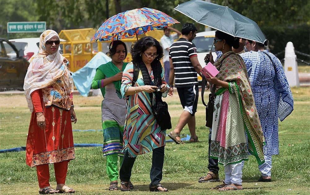 Tourists trying to protect themselves from scorching heat in New Delhi.