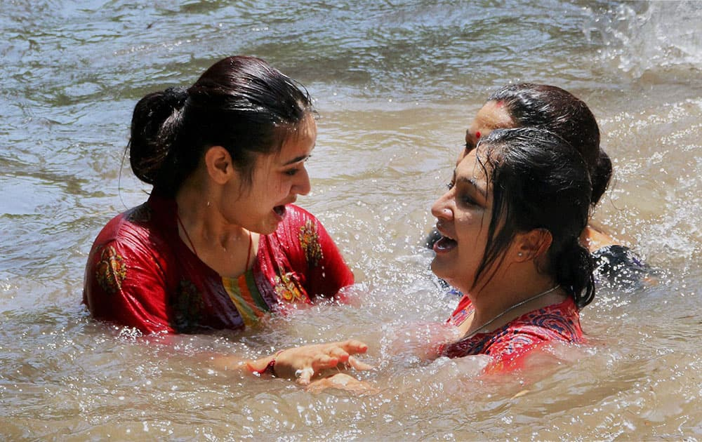 Ladies take a dip in Ranbir Canal to beat the heat on a hot day in Jammu.