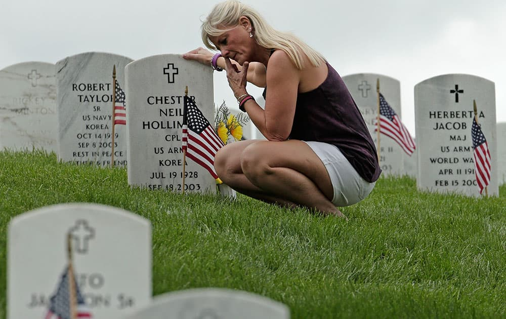 Mary Vanderpool pauses at her parents' grave at the Leavenworth National Cemetery on Memorial Day, in Leavenworth, Kan.