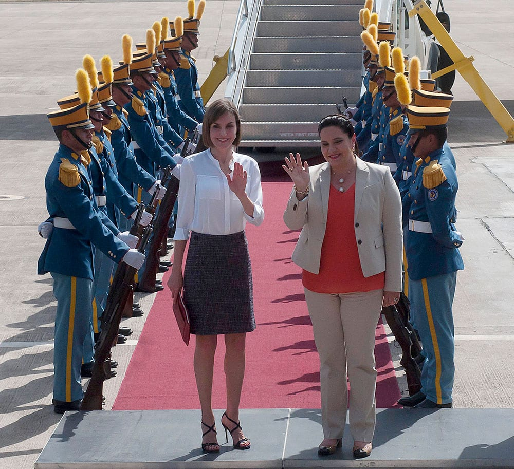 Queen Letizia of Spain, center left, and Honduras' first lady Ana Garcia wave to the press after the Queen arrived at the Palmerola air base near Comayagua, Honduras.