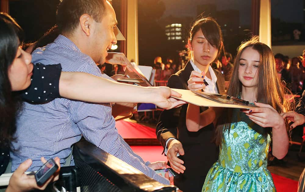 British actress Raffey Cassidy gives her autographs to fans as she arrives for the Japan premiere of the latest Disney film Tomorrowland in Tokyo.