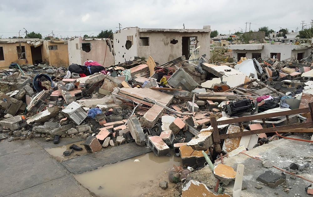 Damaged homes stand next to others that were razed when a powerful tornado touched down. The tornado raged through the city on the US-Mexico border.