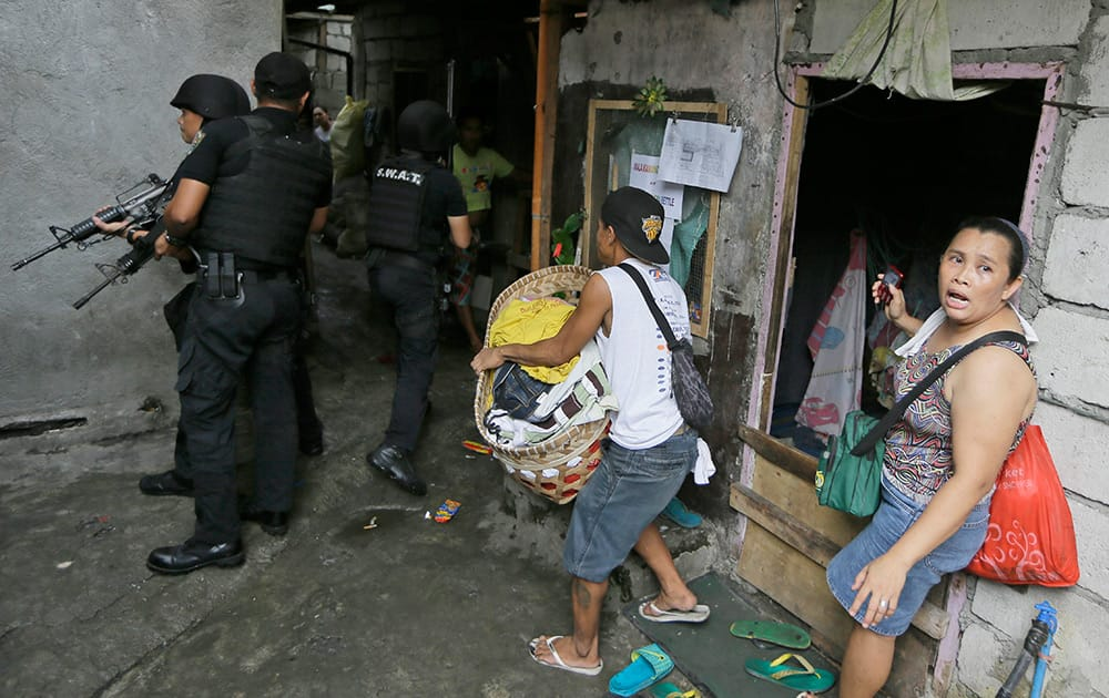 Members of the Philippine National Police conduct a house-to-house search for residents during the demolition of a squatters' community at suburban Caloocan city, north of Manila, Philippines.